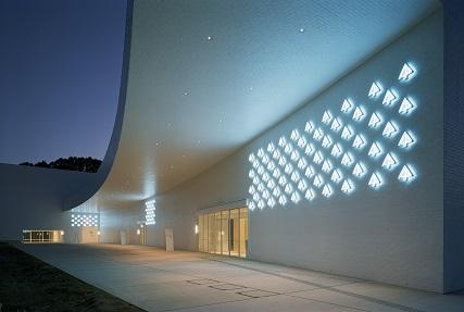 """青森県立美術館外観 入口上のネオンサインは、art,aomor iの頭文字aから発想された青い木 のようなシンボルマークが集まって""""アートの青い森""""として広がっていくことを象徴している。"""
